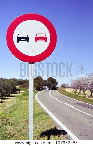 no overtaking sign in a secondary road bordered for olive trees and almond trees in full bloom