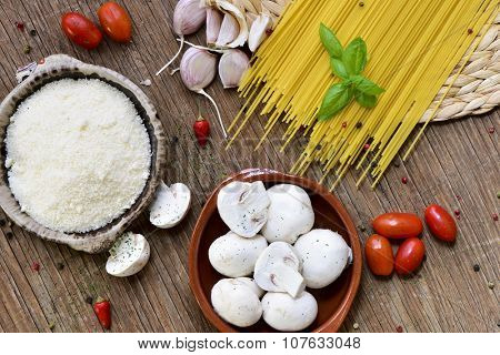 high-angle shot of a rustic wooden table with the ingredients to prepare a recipe of pasta, such as grated cheese, garlics, mushrooms, cherry tomatoes and spaghetti