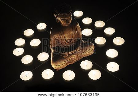 Wooden statue of Buddha with candles around him