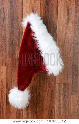 Santa Claus hat hanging from a nail on a rustic wooden wall.  Closeup in vertical format.