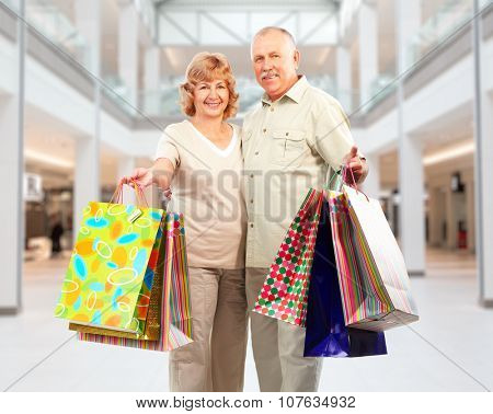 Shopping couple with paper bags in a shopping mall .