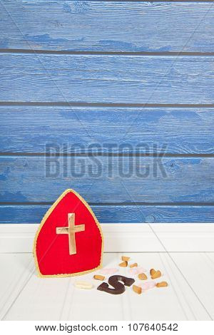 Dutch Sinterklaas candy and mitre on blue background