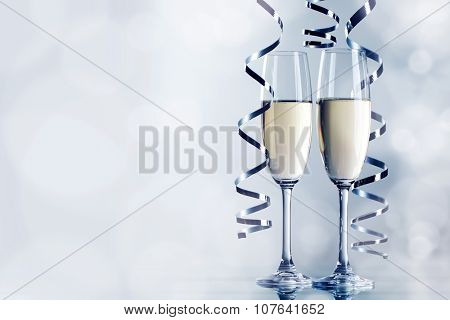 Two glasses of champagne and ribbons on light bokeh background