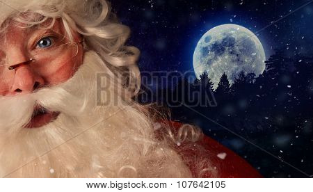 Closeup of Santa Claus with night sky and moon in background