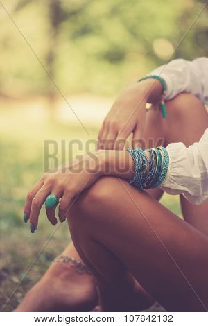 turquoise ring and bracelets on woman hand sit barefoot on grass in wood, closeup,  warm summer day, selective focus,