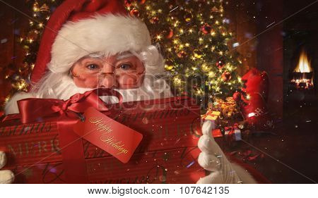 Closeup of Santa Claus holding gift with Christmas scene in background