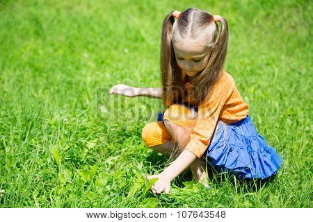 Lovely girl catches a grasshopper in the grass in park