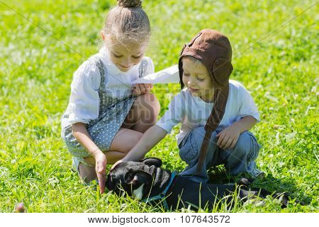 Joyful kids playing with the dog (French bulldog) on the grass. Brother and sister.