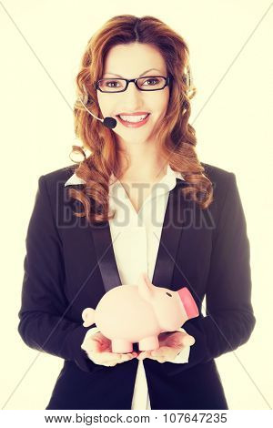 Business woman with headset holding piggy bank.