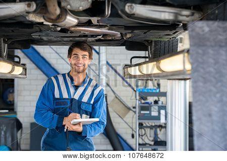 Portrait of happy male mechanic writing on clipboard under car in garage