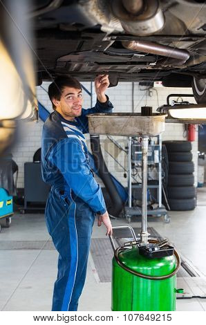 Reliable looking mechanic, checking the oil of a car on a car lift in a garage