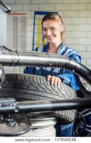Portrait of smiling female mechanic holding car tire in garage