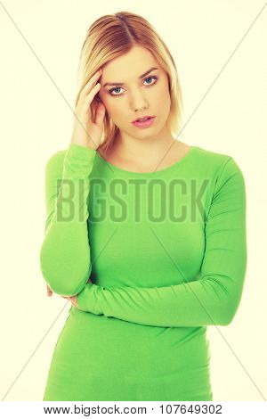 Annoyed young woman holding her head.
