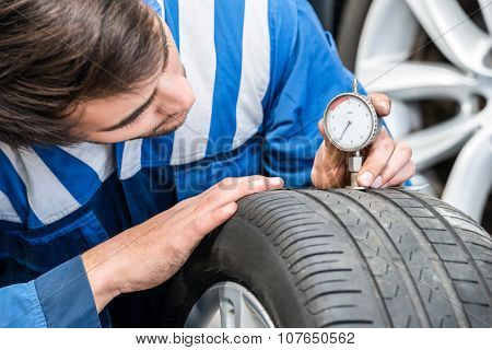 Mechanic pressing gauge into tire tread to measure its depth in garage