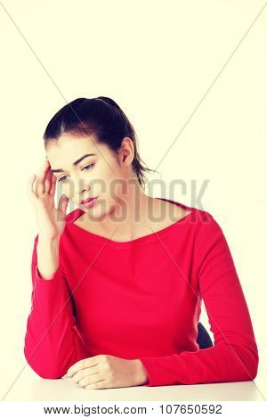 Girl sitting with resigned position. Bored young woman touching her head.