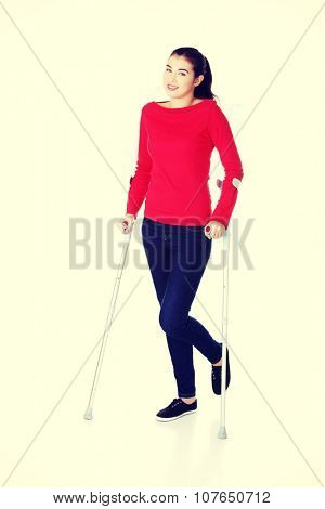 Woman walking with crutches becouse of leg injury