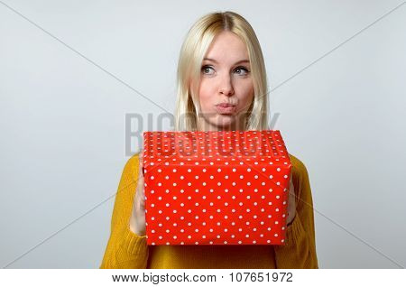 Thoughtful Woman With Pouting Lips Holding Present