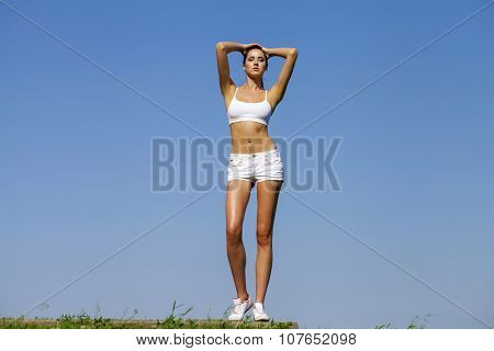 Young tall, slender woman performing sports exercises in a summer park on a background of blue sky