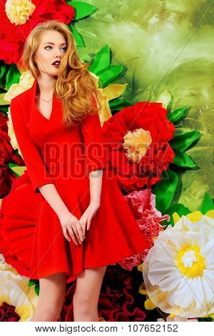 Romantic fashion woman with magnificent blonde hair posing on a background of bright large flowers. Beauty, fashion. The spirit of summer.