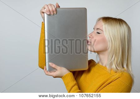 Young Woman Kissing Her Laptop Computer