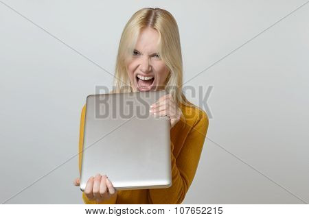 Angry Young Woman Holding Her Laptop Computer