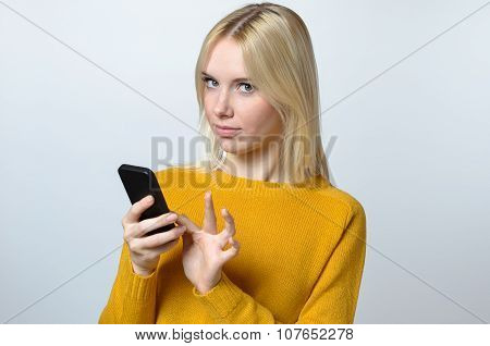 Young Woman Looking At The Camera With Her Mobile Phone