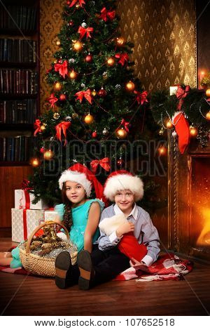 Two cute children in Santa hats sitting with gifts by the Christmas tree at home. The magic of Christmas.