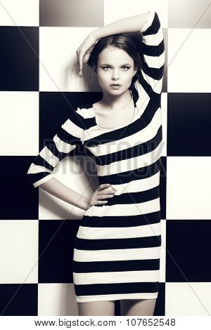 Fashion shot of an elegant model posing in dress in black and white stripes on a background of black and white squares. Beauty, fashion concept. Black-and-white photo.