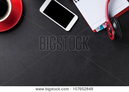Office leather desk with notepad, coffee cup, smartphone and headphones. Top view with copy space