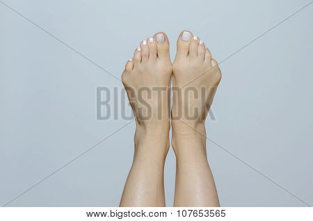 Bare Feet Pointing Up Against Gray Background