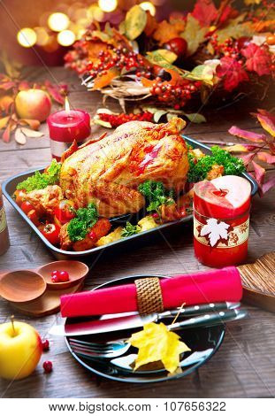 Thanksgiving Dinner. Thanksgiving table served with turkey, decorated with bright autumn leaves. Roasted turkey, table setting. Vertical photo