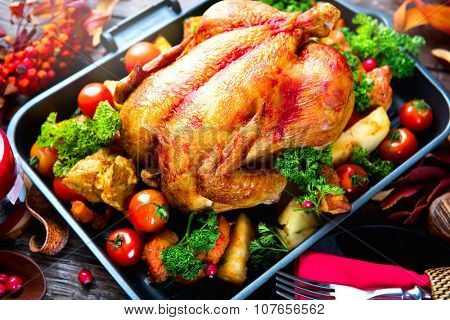 Roasted turkey garnished with Potato, Vegetables and cranberries on a rustic style table decorated with autumn leaves. Thanksgiving Dinner