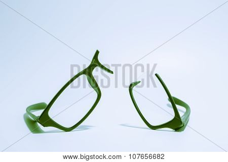 Broken plastic Eyeglasses on colored background