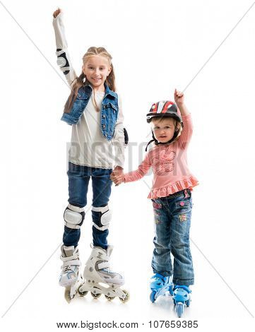two smiling little girls on rollerskates isolated on white background