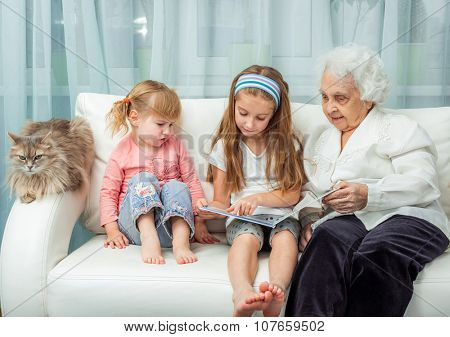 elderly woman with granddaughters reading book on sofa with cat