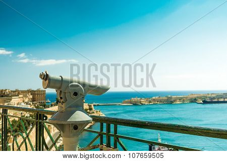 an observation deck with panoramic view of Valletta, Malta and telescope in the foreground
