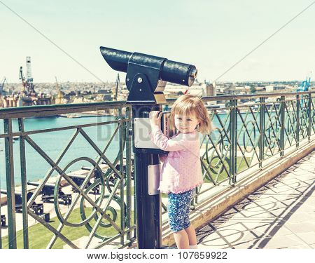 an observation deck with little girl and telescope in the foreground Valletta, Malta