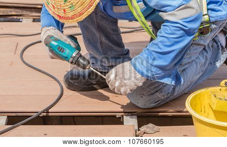 Man With Electric Drill At The Work On Backgrond.