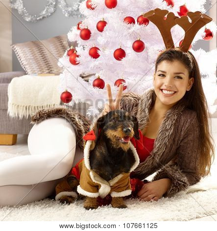 Beautiful young woman celebrating christmas with dog, smiling, looking at camera.