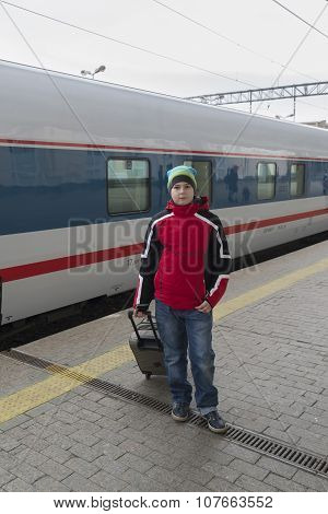 Boy teenager with  travel bag near a train