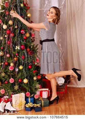Woman dressing Christmas tree and putting gift.