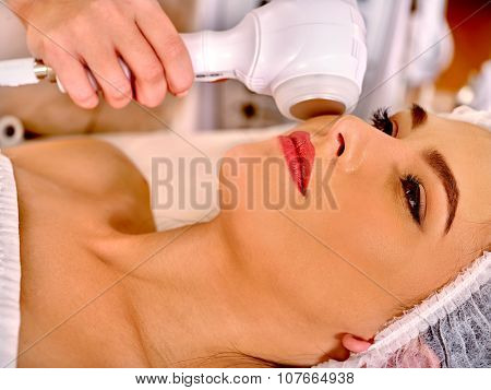 Close up of young woman in hat receiving electric ultrasonic facial massage at beauty salon.