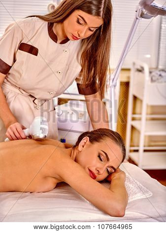 Young white  woman  receiving electric microdermabrasion massage at beauty salon. In room is device for hardware cosmetology.