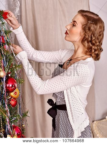 Woman dressing Christmas tree at home.