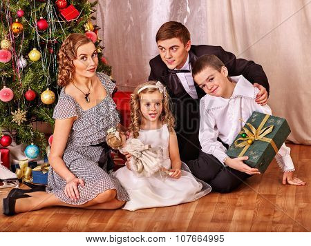 Happy family with children  sitting on floor receiving gifts under Christmas tree. Black and white retro.