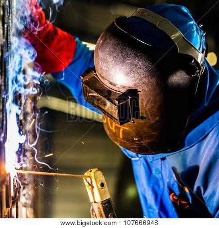 Welder working in an industrial setting manufacturing steel equipment