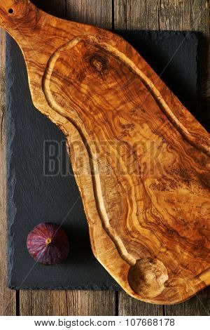 Olive wood cutting board and fig over slate
