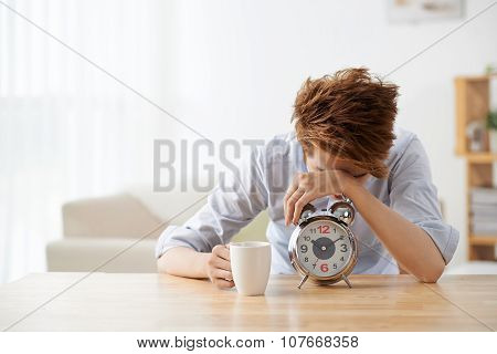Sleepy young man with alarm clock and coffee