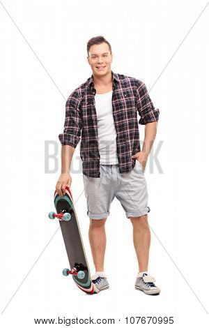 Full length portrait of a young skater holding a skateboard and looking at the camera isolated on white background