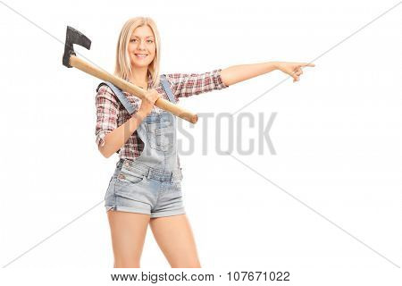 Female worker in overalls holding an axe and pointing to the right with her hand isolated on white background